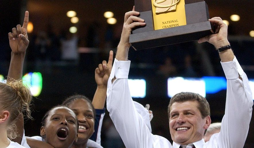 FILE - In this April 6, 2004, file photo, Connecticut coach Geno Auriemma hoists the championship trophy after UConn beat Tennessee 70-61 in the NCAA Division 1 Women's championship game in New Orleans. Auriemma could win his 10th championship and the tie the record held by former UCLA coach John Wooden with a win Tuesday night, April 7, 2015, against Notre Dame. (AP Photo/Mark Humphrey, File)