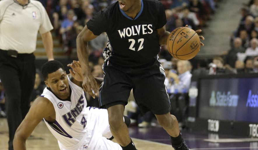 Minnesota Timberwolves forward Andrew Wiggins, right, escapes the defensive pressure of Sacramento Kings forward Rudy Gay, who tumbled to the floor during the first quarter of an NBA basketball game in Sacramento, Calif., Calif., Tuesday, April 7, 2015.(AP Photo/Rich Pedroncelli)