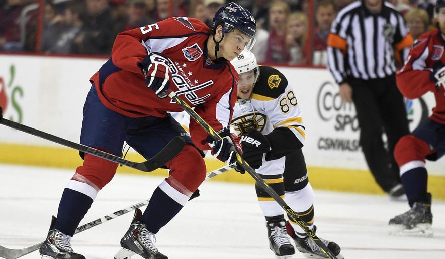 Washington Capitals left wing Andre Burakovsky (65), of Austria, skates with the puck against Boston Bruins right wing David Pastrnak (88) during the first period of an NHL hockey game, Wednesday, April 8, 2015, in Washington. (AP Photo/Nick Wass)
