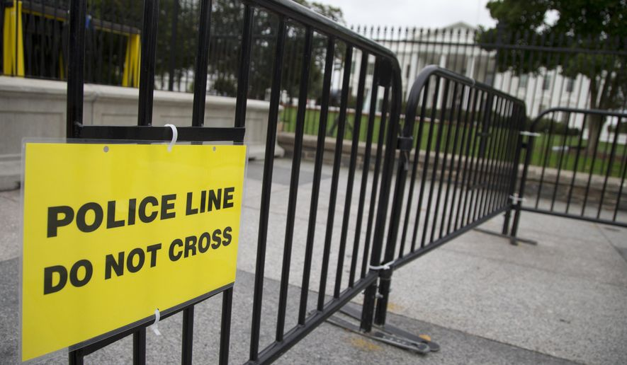 """FILE - In this Oct. 3, 2014, file photo, a temporary barrier marked with a sign """"Police Line Do Not Cross"""" is seen along Pennsylvania Avenue in front of the White House in Washington. The Secret Service has placed a high-ranking supervisor on administrative leave and suspended the supervisor's security clearance after what it calls """"allegations of misconduct and potential criminal activity."""" (AP Photo/Carolyn Kaster, File)"""