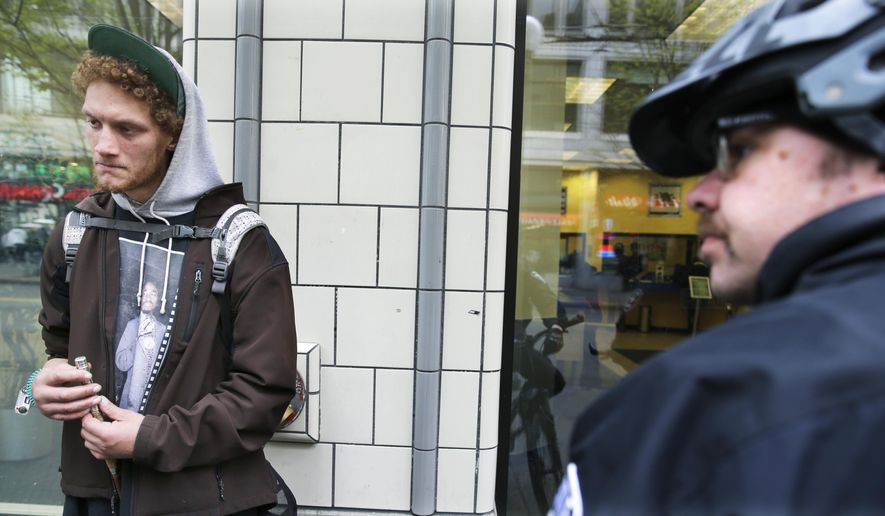 Gailen Lopton, left, talks with Seattle police Officer Matt Chase, right, as he hangs out in downtown Seattle, Tuesday, April 7, 2015. When Lopton was caught injecting heroin by police in a downtown alley in March, the officers offered him a chance to enroll in a first-of-its-kind program called Law Enforcement Assisted Diversion, aimed at keeping low-level drug offenders and prostitutes out of jail and receiving services for housing, counseling and job training. A study released Wednesday, April 8, 2015 by the University of Washington found encouraging signs of the program's effectiveness, and other cities are hoping to start programs of their own. (AP Photo/Ted S. Warren)