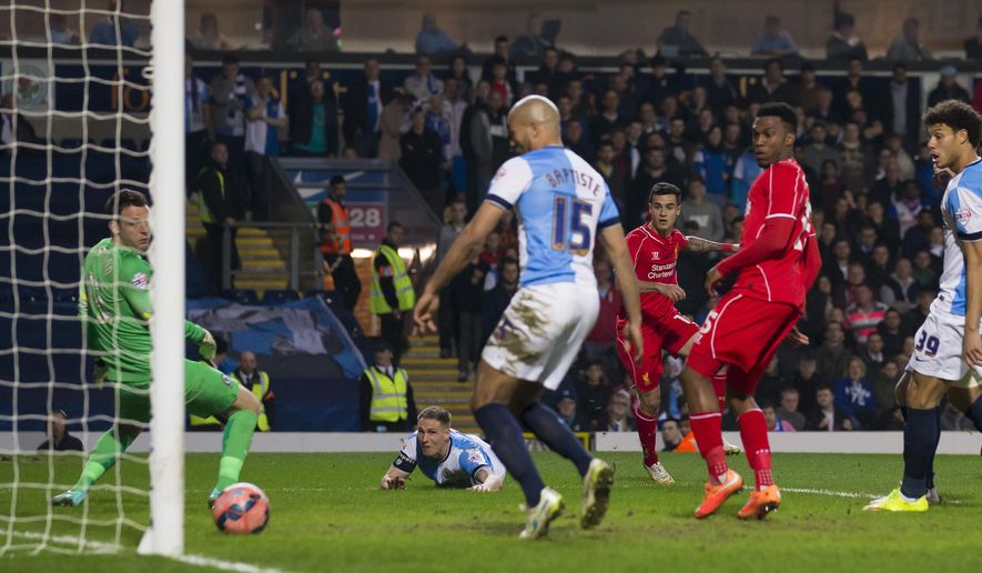 Liverpool's Philippe Coutinho, centre right, scores past Blackburn's goalkeeper Simon Eastwood, left, during the English FA Cup sixth round replay soccer match between Blackburn and Liverpool at Ewood Park Stadium, Blackburn, England, Wednesday, April 8, 2015. (AP Photo/Jon Super)