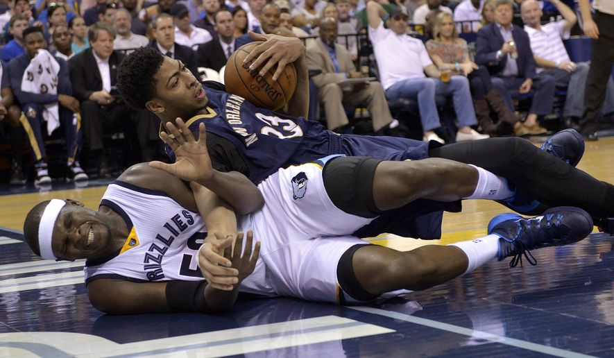 New Orleans Pelicans forward Anthony Davis (23) and Memphis Grizzlies forward Zach Randolph (50) fall to the court during the first half of an NBA basketball game Wednesday, April 8, 2015, in Memphis, Tenn. (AP Photo/Brandon Dill)