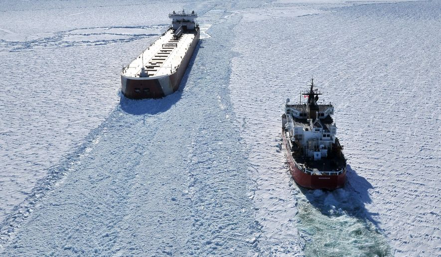 FILE-- In this March 27, 2015 file photo, the U. S. Coast Guard cutter Mackinaw, right, works in thick ice to break out the freighter Edwin Gott in Whitefish Bay of Lake Superior. Crews are working to clear a path through ice on eastern Lake Superior that's left freighters unable to move, including one that had a hole punched in its hull. Officials say at least 10 ships are affected.(AP Photo/John L. Russell, File)