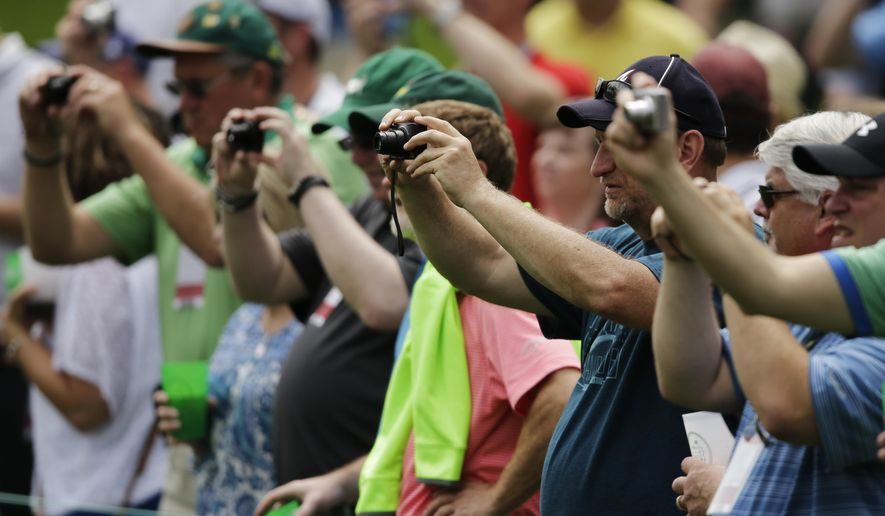 Spectators take photos of Bubba Watson on the third hole during a practice round for the Masters golf tournament Monday, April 6, 2015, in Augusta, Ga. (AP Photo/Matt Slocum)