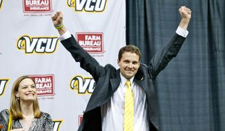 New VCU college basketball coach Will Wade gestures at a news conference as his wife, Lauren, looks on Wednesday, April 8, 2015, in Richmond, Va.  (AP Photo/Richmond Times-Dispatch, Mark Gormus)