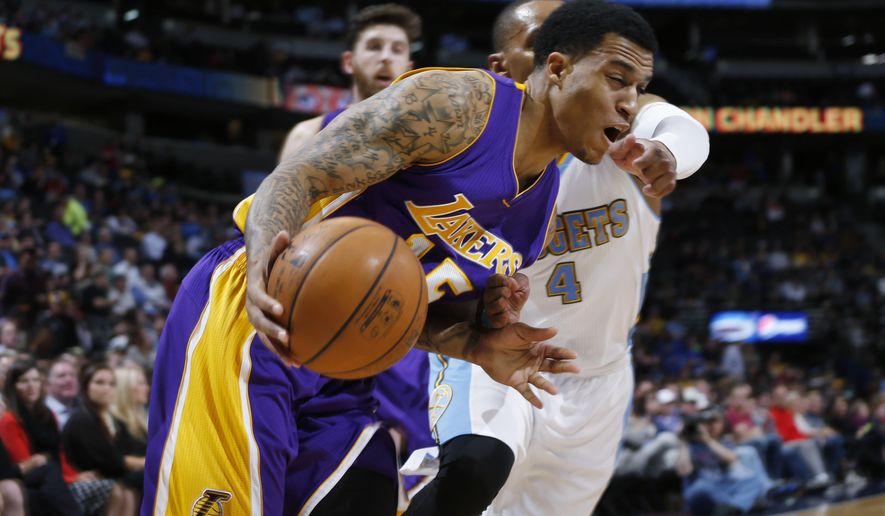 Los Angeles Lakers guard Jabari Brown, front, reacts as he gets hit in the face while driving for a shot by Denver Nuggets guard Randy Foye (4) in the first quarter of an NBA basketball game Wednesday, April 8, 2015, in Denver. (AP Photo/David Zalubowski)