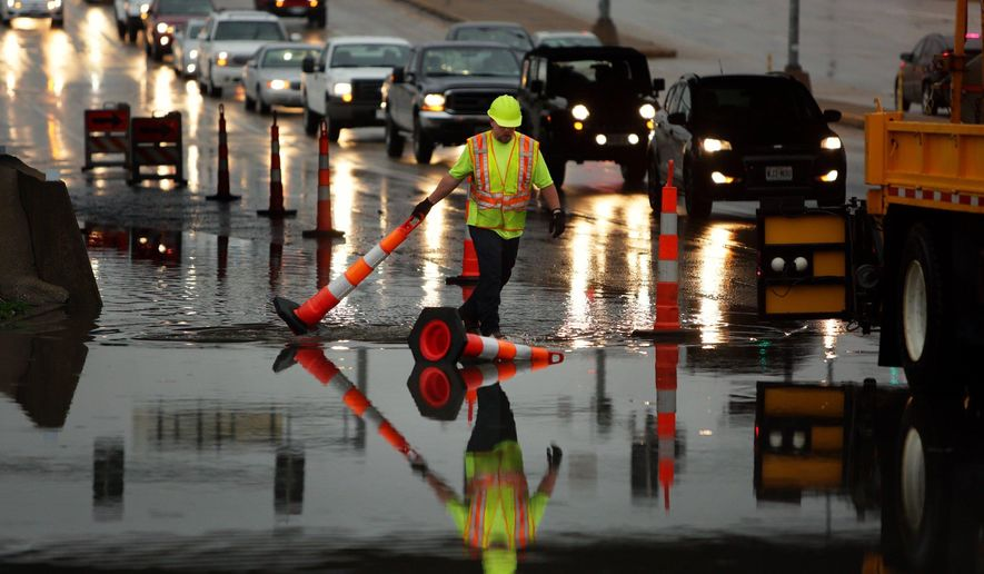 A Missouri Department of Transportation worker adjusts cones on a flooded section of south bound Route 141 underneath Interstate 44 after a storm flooded the area on Tuesday, April 7, 2015 near Valley Park, Mo. (AP Photo/St. Louis Post-Dispatch, Huy Mach)  EDWARDSVILLE INTELLIGENCER OUT; THE ALTON TELEGRAPH OUT; MANDATORY CREDIT
