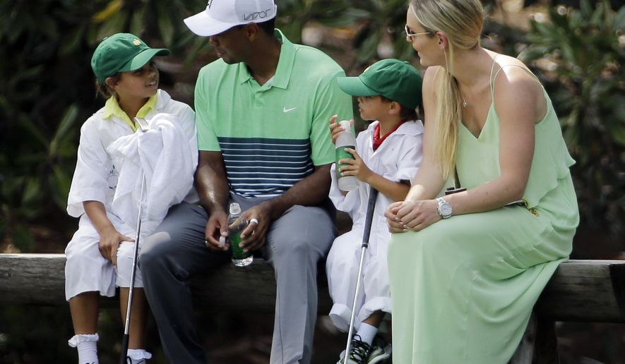 Lindsey Vonn sits with Tiger Woods with his children Sam and Charlie during the Par 3 contest at the Masters golf tournament Wednesday, April 8, 2015, in Augusta, Ga. (AP Photo/David J. Phillip)
