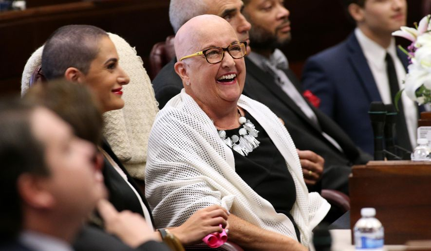Nevada Sen. Debbie Smith, D-Sparks, center, is recognized on the Senate floor at the Legislative Building in Carson City, Nev., on Wednesday, April 8, 2015. Smith returned to work Wednesday, two months after having a malignant brain tumor removed. Her daughter Erin Marlon, on her right, and husband Greg, on her left, both shaved their heads with her. (AP Photo/Cathleen Allison)