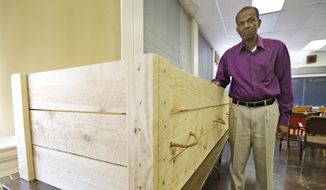 The Rev. Alfred L. Jones III poses with a period style pine box coffin that will be used to represent former slave Hannah Reynolds, who was the lone civilian death at Appomattox at the end of the war, at the Carver-Price Legacy Museum in Appomattox, Va., Wednesday, April 1, 2015. Jones will deliver the eulogy for Reynolds whose death will be remembered during the 150th anniversary of the Civil War's end. (AP Photo/Steve Helber)