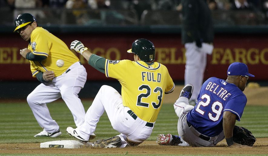 Oakland Athletics' Sam Fuld (23) slides in for a triple as Texas Rangers third baseman Adrian Beltre (29) misses the throw from the outfield during the sixth inning of a baseball game Tuesday, April 7, 2015, in Oakland, Calif. (AP Photo/Marcio Jose Sanchez)