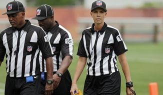 FILE - In this June 12, 2014, file photo, Sarah Thomas, right, walks off the field after a Cleveland Browns mandatory minicamp practice at the NFL football team's facility in Berea, Ohio. Officials at left are unidentified. The NFL has its first full-time female game official. Sarah Thomas, who has worked exhibition games, will be a line judge for the 2015 season, the league announced Wednesday, April 8, 2015. (AP Photo/Mark Duncan, File)