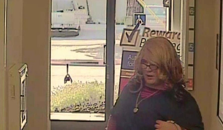 """This Friday, April 3, 2015, image from surveillance video provided by the Santa Cruz Police Department shows a wanted man dubbed the """"Mrs. Doubtfire"""" bandit because he was disguised as a woman during a bank robbery in Santa Cruz, Calif. He wore a wavy blonde wig, thick-framed glasses and navy blue hospital scrubs, and carried a purse. About an hour later the same man in the same outfit handed a teller a note that demanded money at a second US Bank branch in Santa Cruz. The suspect got away with an unknown amount of money.  (AP Photo/Santa Cruz Police Department)"""