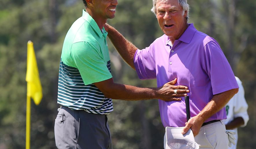 Tiger Woods, left, and Ben Crenshaw embrace on the 18th green as they finish a practice round for the Masters golf tournament in Augusta, Ga., Wednesday, April 8, 2015. (AP Photo/Atlanta Journal-Constitution, Curtis Compton)  MARIETTA DAILY OUT, GWINNETT DAILY POST OUT) LOCAL STATIONS OUT (WXIA, WGCL, FOX 5)