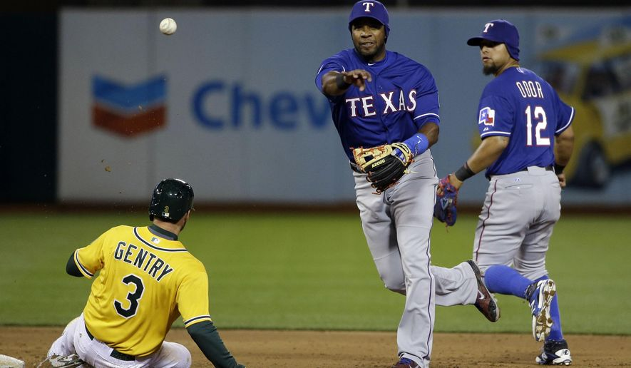 Texas Rangers shortstop Elvis Andrus, center, turns a double play over Oakland Athletics' Craig Gentry (3) on a ground ball from Sam Fuld during the third inning of a baseball game Tuesday, April 7, 2015, in Oakland, Calif. (AP Photo/Marcio Jose Sanchez)