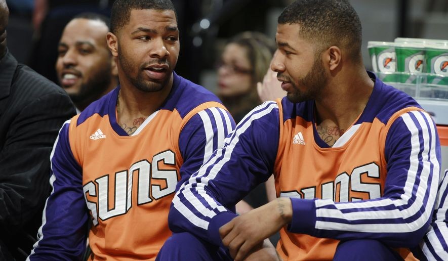 FILE - In this Feb. 18, 2014, file photo, Phoenix Suns forwards Marcus Morris, left, and his twin brother Markieff talk on bench as the Suns play the Denver Nuggets in the first quarter of an NBA basketball game in Denver. The Phoenix Suns' Marcus and Markieff Morris are being investigated on allegations that they beat a former mentor, Wednesday, April 8, 2015. (AP Photo/David Zalubowski, File)