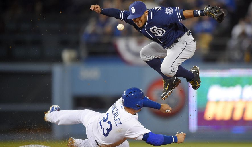 San Diego Padres shortstop Alexi Amarista, right, loses control of the ball and a chance at a double play after forcing out Los Angeles Dodgers' Adrian Gonzalez at second on a ball hit by Howie Kendrick during the fourth inning of a baseball game, Tuesday, April 7, 2015, in Los Angeles. (AP Photo/Mark J. Terrill)