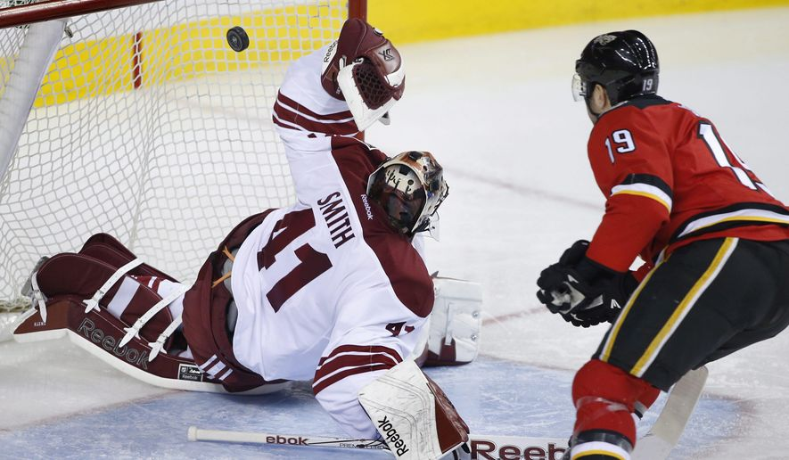 Arizona Coyotes goalie Mike Smith, left, gives up a goal to Calgary Flames' David Jones during the third period of an NHL hockey game Tuesday, April 7, 2015, in Calgary, Alberta. (AP Photo/The Canadian Press, Larry MacDougal)