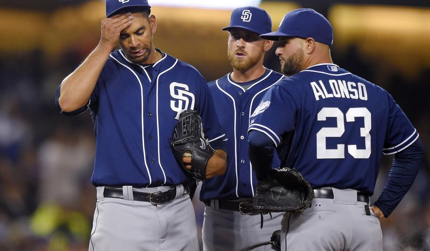 San Diego Padres starting pitcher Tyson Ross, left, rubs his head as third baseman Will Middlebrooks, center, and first baseman Yonder Alonso wait after Los Angeles Dodgers' Adrian Gonzalez scored on a single by Howie Kendrick during the sixth inning of a baseball game, Tuesday, April 7, 2015, in Los Angeles. (AP Photo/Mark J. Terrill)