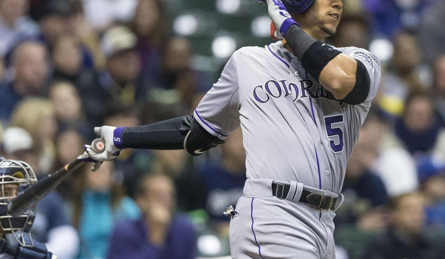 Colorado Rockies' Carlos Gonzalez hits a two run homer off of Milwaukee Brewers' Jonathan Broxton during the eighth inning of a baseball game Wednesday, April 8, 2015, in Milwaukee. (AP Photo/Tom Lynn)