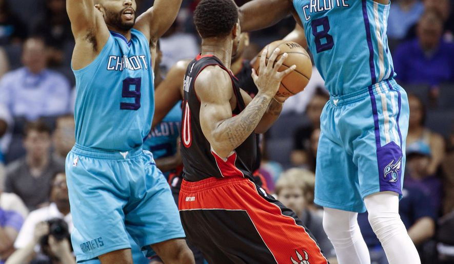 Toronto Raptors guard DeMar DeRozan, center, looks to pass against the double team by Charlotte Hornets forward Gerald Henderson, left, and center Bismack Biyombo in the first half of an NBA basketball game Wednesday, April 8, 2015 in Charlotte, N.C. (AP Photo/Nell Redmond)