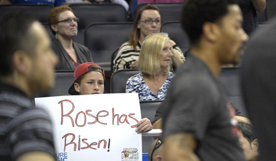 Chicago Bulls fan Blair Lamphier holds a sign as Chicago Bulls' Derrick Rose, right, huddles with the team during a timeout in the first half of an NBA basketball game against the Orlando Magic in Orlando, Fla., Wednesday, April 8, 2015. (AP Photo/Phelan M. Ebenhack)
