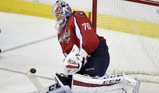 Washington Capitals goalie Braden Holtby reaches for the puck during the third period of an NHL hockey game against the Boston Bruins, Wednesday, April 8, 2015, in Washington. The Capitals won 3-0. (AP Photo/Nick Wass)