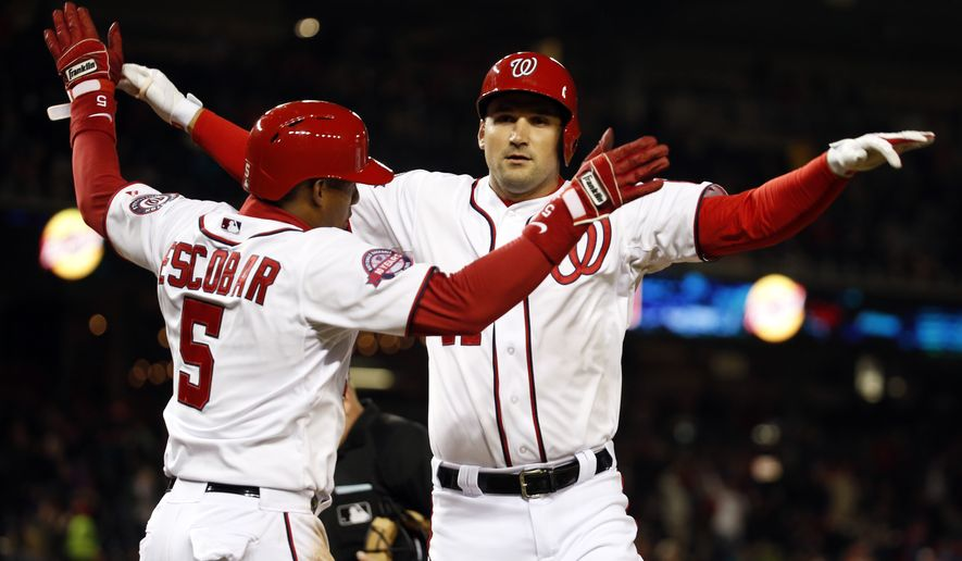 Washington Nationals' Ryan Zimmerman, right, celebrates his two-run homer with Yunel Escobar (5) during the  first inning of a baseball game against the New York Mets at Nationals Park, Wednesday, April 8, 2015, in Washington. (AP Photo/Alex Brandon)