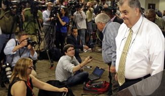 Police Chief Eddie Driggers, right, and Mayor Keith Summey, back, leave after a news conference about the shooting death of Walter Scott at city hall in North Charleston, S.C., Wednesday, April 8, 2015. Scott was killed by a North Charleston police officer after a traffic stop on Saturday.  The officer, Michael Thomas Slager, has been charged with murder. (AP Photo/Chuck Burton)