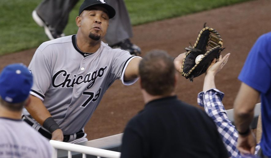Chicago White Sox first baseman Jose Abreu reaches into the crowd to catch a foul ball hit by Kansas City Royals' Alcides Escobar during the first inning of a baseball game at Kauffman Stadium in Kansas City, Mo., Wednesday, April 8, 2015. (AP Photo/Orlin Wagner)