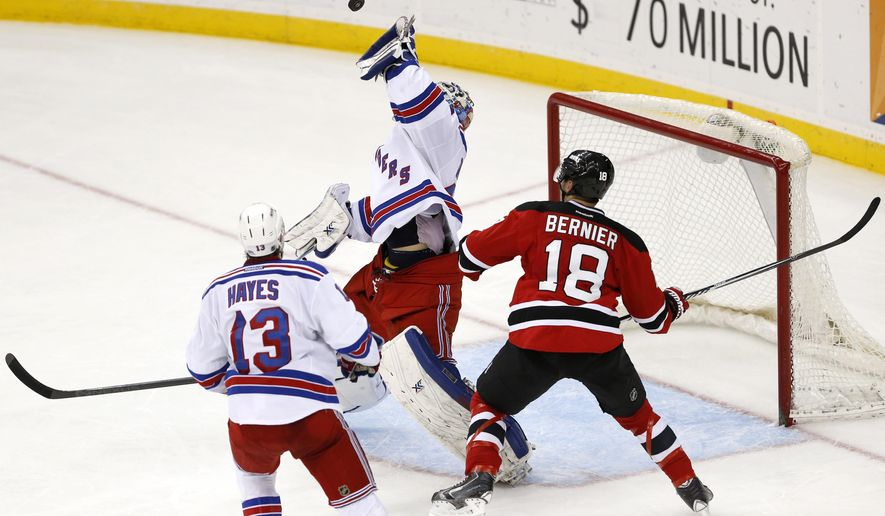 New York Rangers goalie Cam Talbot, center, reaches for the puck as New Jersey Devils right wing Steve Bernier (18) attacks during the third period of an NHL hockey game, Tuesday, April 7, 2015, in Newark, N.J. The Rangers won 4-2. Rangers' right wing Kevin Hayes (13) looks on during the play.  (AP Photo/Julio Cortez)