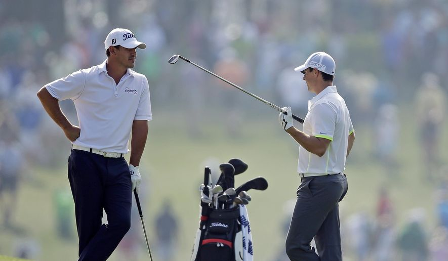 Brooks Koepka, left, speaks to Rory McIlroy, of Northern Ireland, on the first fairway during a practice round for the Masters golf tournament Wednesday, April 8, 2015, in Augusta, Ga. (AP Photo/Matt Slocum)