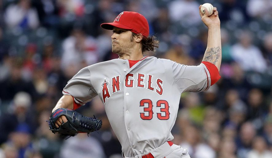 Los Angeles Angels starting pitcher C.J. Wilson throws against the Seattle Mariners during the first inning of a baseball game Tuesday, April 7, 2015, in Seattle. (AP Photo/Elaine Thompson)