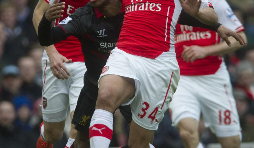 Arsenal's Francis Coquelin, right, controls the ball in front of Liverpool's Raheem Sterling, during their English Premier League soccer match, at Emirates Stadium, in London, Saturday, April 4, 2015. (AP Photo/Bogdan Maran)