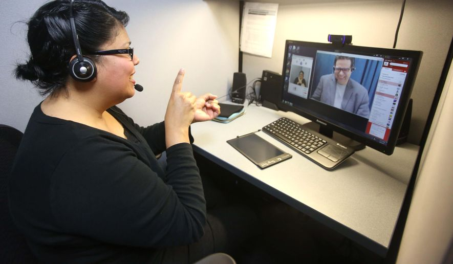 Faridna Hunter uses American Sign Language to speak to a remote client over the internet at ASL Services in Kissimmee, Fla. She can translate signing into speech, and speech into signing. ASL Services is growing into one of the nation's largest sign-language call centers. Technology like Skype and video-conferencing are making this more possible. (AP Photo/Orlando Sentinel, George Skene. File Feb. 27, 2015 )