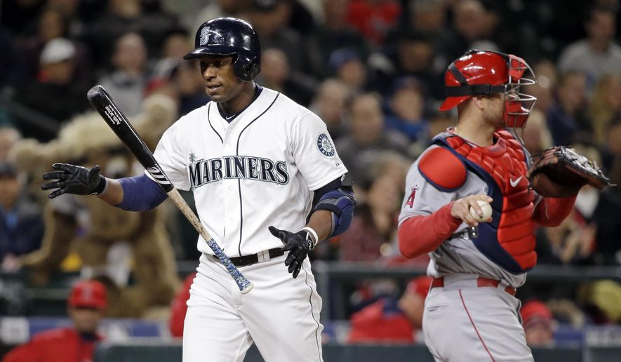Seattle Mariners' Austin Jackson, left, flips his bat after striking out, while Los Angeles Angels catcher Chris Iannetta waits for the next batter in the ninth inning of a baseball game Tuesday, April 7, 2015, in Seattle. The Angels won 2-0. (AP Photo/Elaine Thompson)