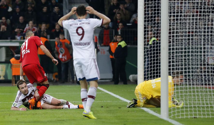 Bayern's Mario Goetze, bottom left, is comforted by Leverkusen's Omer Toprak from Turkey after he failed to score during the German soccer cup (DFB Pokal) quarterfinal match between Bayer 04 Leverkusen and Bayern Munich Wednesday, April 8, 2015 in Leverkusen, Germany. (AP Photo/Frank Augstein)
