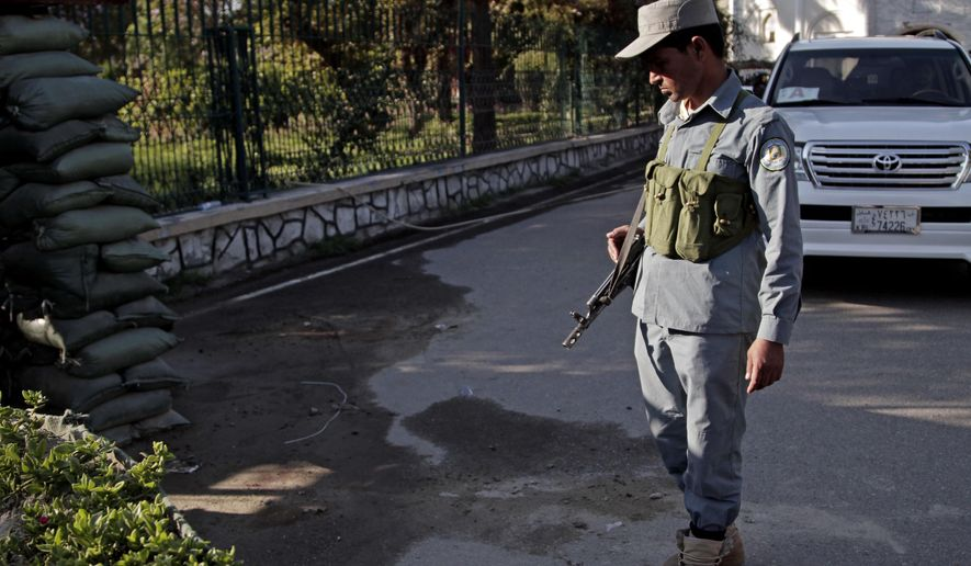 An Afghan policeman looks at a bloodstained pavement at the site of an attack by an Afghan national army soldier who opened fire on U.S. troops, at the compound of the provincial governor, in Jalalabad, Afghanistan, Wednesday, April 8, 2015. An American soldier was killed in the shooting Wednesday in which at least two other U.S. troops were wounded. The incident happened after a meeting between Afghan provincial leaders and a U.S. Embassy official. (AP Photo/Rahmat Gul)