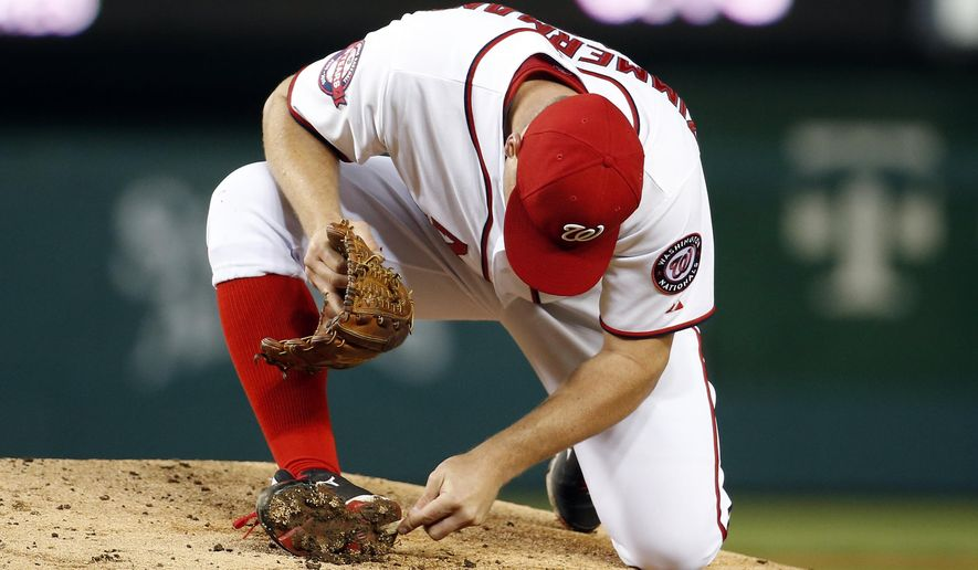Washington Nationals starting pitcher Jordan Zimmermann (27) digs the mud out of his spikes during the fifth inning of a baseball game against the New York Mets at Nationals Park, Wednesday, April 8, 2015, in Washington. (AP Photo/Alex Brandon)