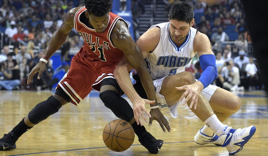 Chicago Bulls guard Jimmy Butler (21) and Orlando Magic center Nikola Vucevic (9) reach for the ball during the first half of an NBA basketball game in Orlando, Fla., Wednesday, April 8, 2015. (AP Photo/Phelan M. Ebenhack)