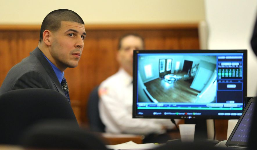 Former New England Patriots football player Aaron Hernandez looks up as his defense attorney, James Sultan shows a video of Hernandez's home as he emerged from the basement, during closing arguments in his trial in Fall River, Mass., Tuesday, April 7, 2015.  Hernandez is accused of killing Odin Lloyd in June 2013.  (AP Photo/The Boston Globe, John Tlumacki, Pool)