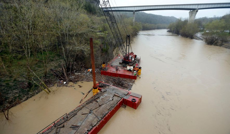 Two barges are secured near the old bridge on the Jessamine Co. side of the Kentucky River at Camp Nelson near Nicholasville, Ky., Tuesday, April 7 2015.  Two barges, one carrying a 100-foot tall crane, drifted about four miles down the Kentucky River during last weekend's flooding without causing any significant damage.   (AP Photo/Lexington Herald-Leader, Charles Bertram)