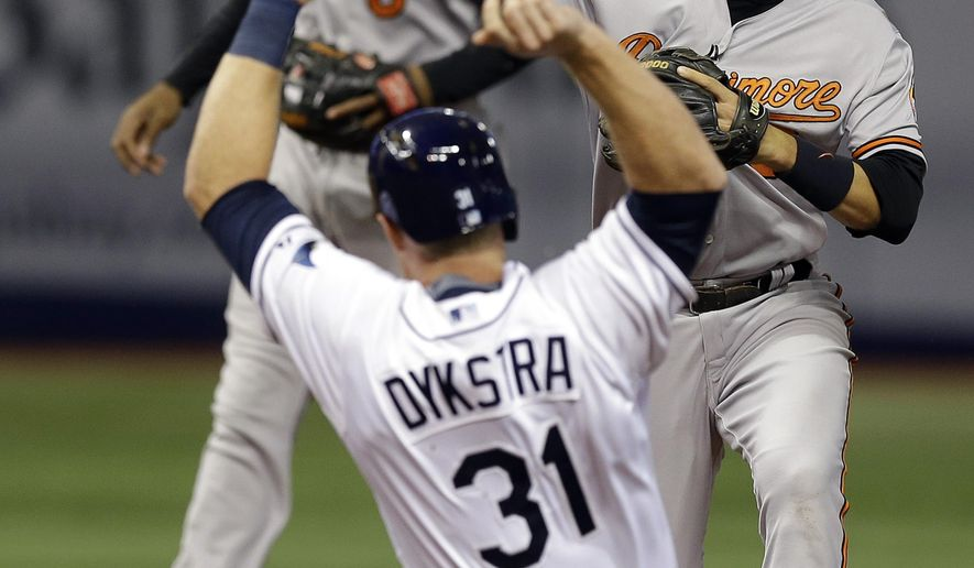 Baltimore Orioles shortstop Ryan Flaherty forces Tampa Bay Rays' Allan Dykstra at second base and relays the throw to first to turn a double play on Rays' Rene Rivera during the fifth inning of a baseball game Wednesday, April 8, 2015, in St. Petersburg, Fla. Backing up the play for the Orioles Jonathan Schoop. (AP Photo/Chris O'Meara)