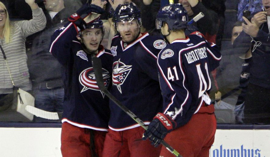 Columbus Blue Jackets' Scott Hartnell, center, celebrates his goal against the Toronto Maple Leafs with teammates Mark Dano, left, and Alexander Wennberg, of Sweden, during the first period of an NHL hockey game Wednesday, April 8, 2015, in Columbus, Ohio. (AP Photo/Jay LaPrete)