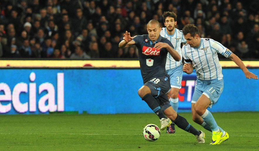 Napoli's Gokhan Inler, left, fights for the ball with Lazio's Miroslav Klose, right, during their Italian Cup semifinal soccer match at the San Paolo stadium in Naples, Italy, Wednesday, April 8, 2015. (AP Photo/Cesare Abbate, Ansa)