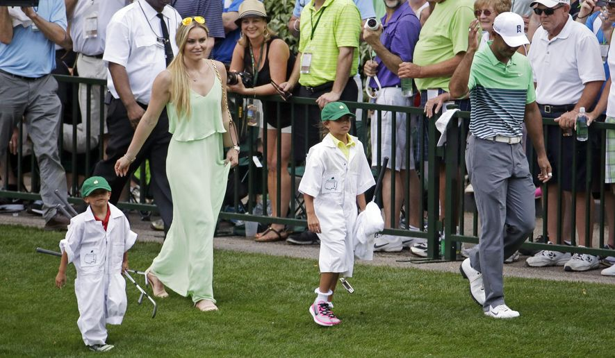 Lindsey Vonn walk Tiger Woods and his children Sam and Charlie during the Par 3 contest at the Masters golf tournament Wednesday, April 8, 2015, in Augusta, Ga. (AP Photo/Charlie Riedel)