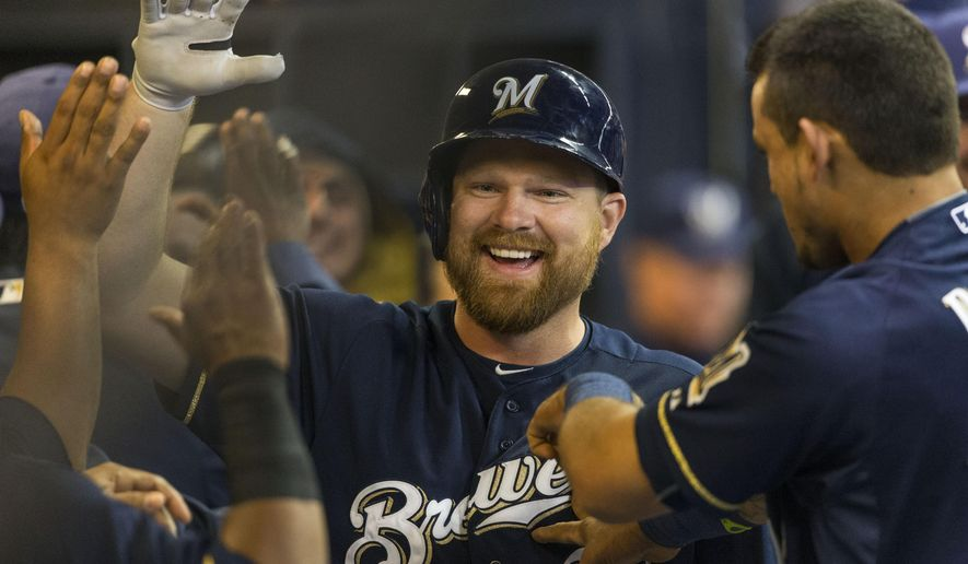 Milwaukee Brewers' Adam Lind is congratulated by teammates after hitting a two run homer off of Colorado Rockies' Eddie Butler during the third inning of a baseball game Wednesday, April 8, 2015, in Milwaukee. (AP Photo/Tom Lynn)