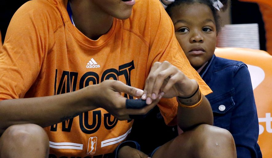 """FILE - In this July 19, 2014, file photo, West's Candace Parker, of the Los Angeles Sparks, sits with her daughter, Laila, during the second half the WNBA All-Star basketball game in Phoenix. Parker will sit out at least the beginning of the upcoming WNBA season to rest. """"It was Candace's decision and she felt she needed to get her body 100 percent healthy,"""" Sparks general manager Penny Toler told The Associated Press.  (AP Photo/Matt York, File)"""