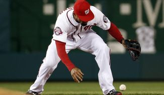 Washington Nationals shortstop Ian Desmond (20) bobbles a ball but gets the out on New York Mets' Daniel Murphy during the ninth inning of a baseball game at Nationals Park, Wednesday, April 8, 2015, in Washington. The Nationals won 2-1. (AP Photo/Alex Brandon)